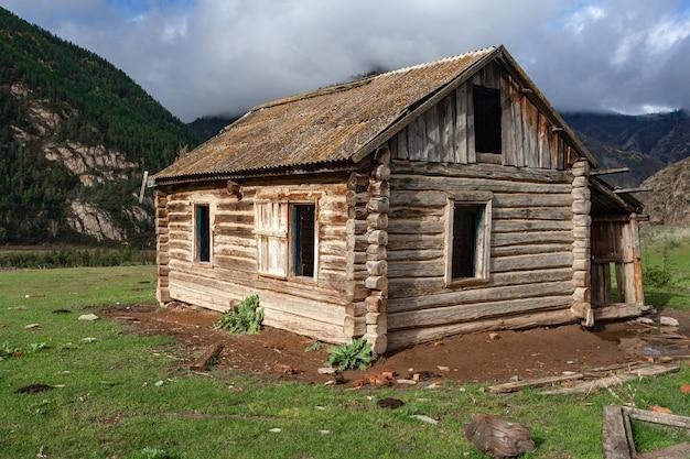 Красивый деревянный заброшенный бревенчатый дом на фоне гор