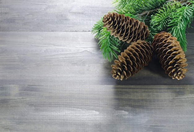 Beautiful wooden background with christmas pine cones in the top right