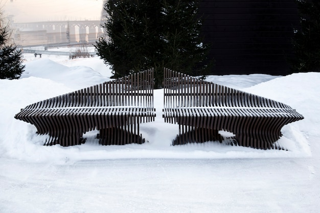 Beautiful wooden bench in the park on a background of snow improvement design public space