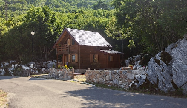 Beautiful wooden hotel standing on side of road at mountains