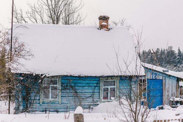 Beautiful wooden house covered with fresh fallen snow.  uninhabited old winter cozy cottage in empty village
