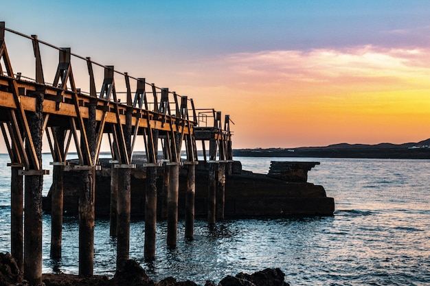 Beautiful wooden pier at the coast of the sea with a beautiful sunset