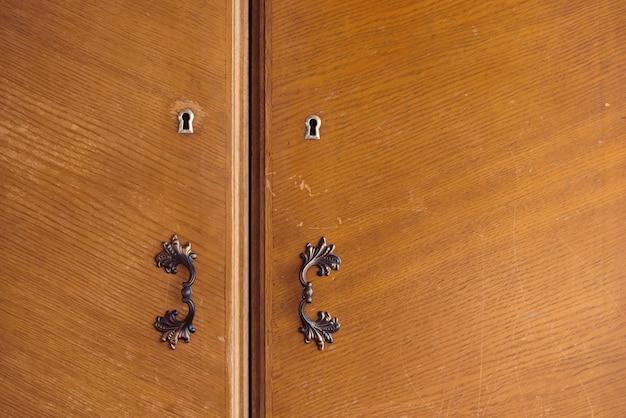 Красивый деревянный ретро шкаф закрыт на ключ. красивые двери шкафа с замочной скважиной и старинные дверные ручки из латуни крупным планом. фоновое изображение дверей grunge деревянных шкафчика.