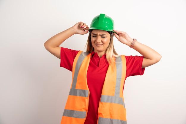 Bella donna operaia che indossa un elmetto protettivo verde su sfondo bianco.