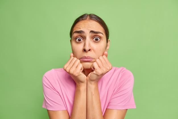 Красивая взволнованная молодая женщина держит руки под подбородком в тревоге, выглядит очень расстроенной, одетая в повседневную розовую футболку, позирует на фоне ярко-зеленой стены