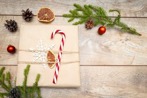 나무 배경 크리스마스에 전나무 가지 사탕 지팡이 장식이 있는 아름다운 포장된 선물 상자