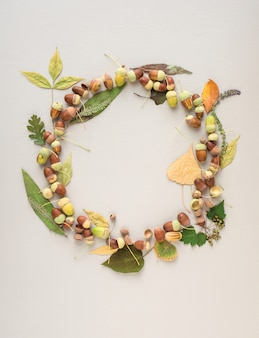 Beautiful wreath made of acorns and different sized leaves on a light purple background