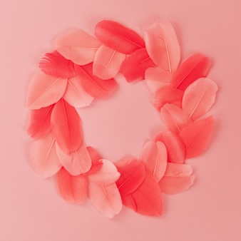 Beautiful wreath made of real feathers trend color pink coral on pink background closeup.