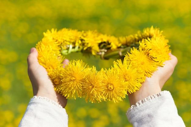 Beautiful wreath of yellow dandelions in child's hands.