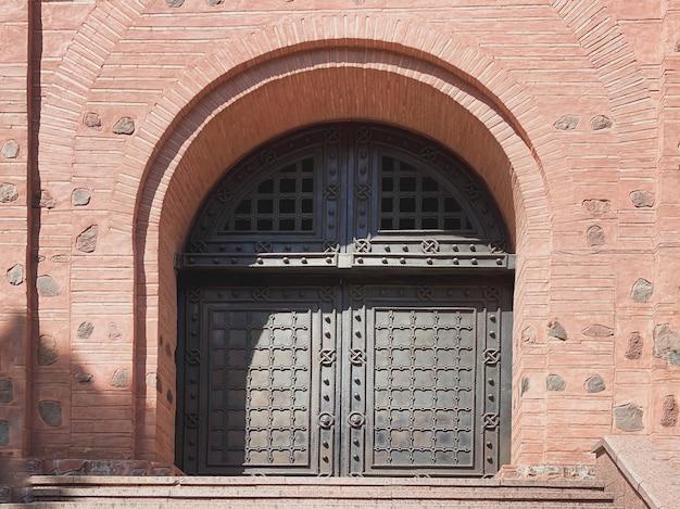 오래된 스타일의 주황색 벽돌 건물에 있는 아름다운 연철 문