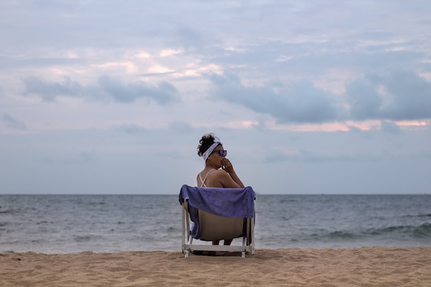 Beautiful yawning girl on a sun lounger on the beach near the ocean in cloudy weather. vacation concept.