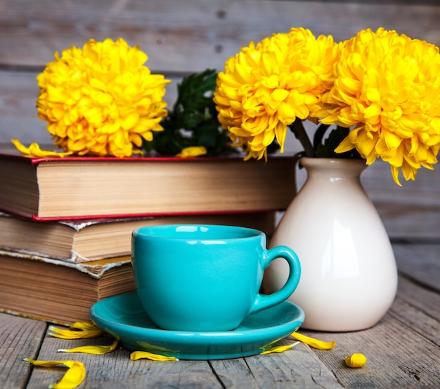 ヴィンテージの花瓶、一杯のコーヒーと本の美しい黄色の菊