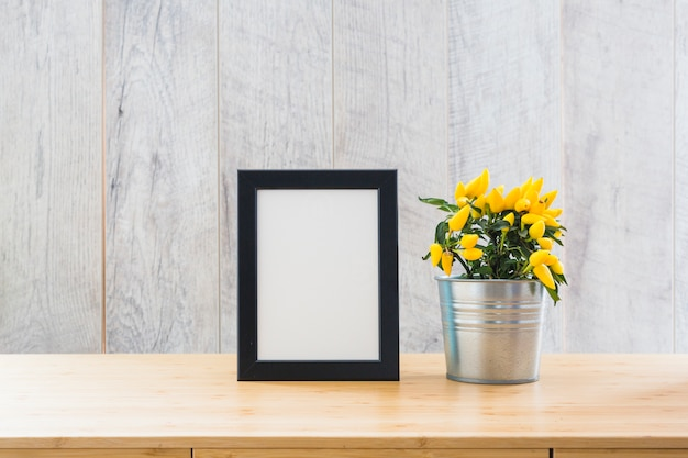 Beautiful yellow hot chili peppers in silver pot and white picture frame on the table