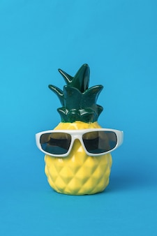 A beautiful yellow pineapple with glasses on a blue background. summer concept.
