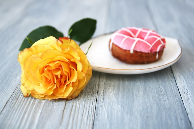 A beautiful yellow rose with an opened bud and a donut with pink icing on a white ceramic plate on a gray wooden