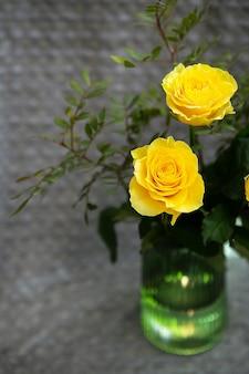 緑の花瓶に美しい黄色いバラが毛布の上に立っています。驚きと休日のコンセプト。閉じる。