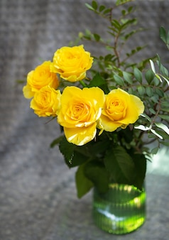 緑の花瓶に美しい黄色いバラが毛布の上に立っています。驚きと休日のコンセプト。