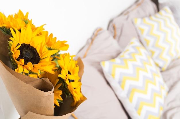 Красивый букет желтых подсолнухов с крафт-бумагой возле кровати в спальне