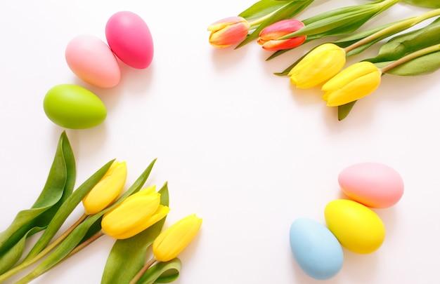 Красивые желтые тюльпаны и красочные пасхальные яйца на белом фоне, вид сверху.