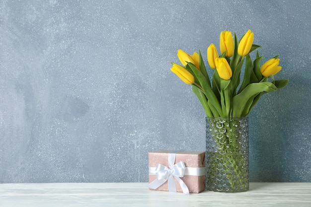Beautiful yellow tulips in glass vase on wooden table and space for text