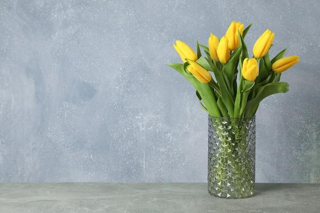Красивые желтые тюльпаны в стеклянной вазе на сером на день матери. пространство для текста