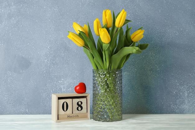 Красивые желтые тюльпаны в стеклянной вазе на белом на день матери