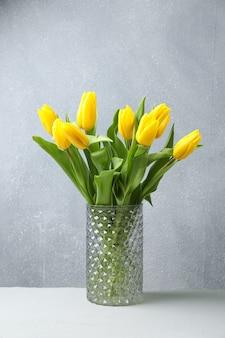 Красивые желтые тюльпаны в стеклянной вазе на деревянном столе