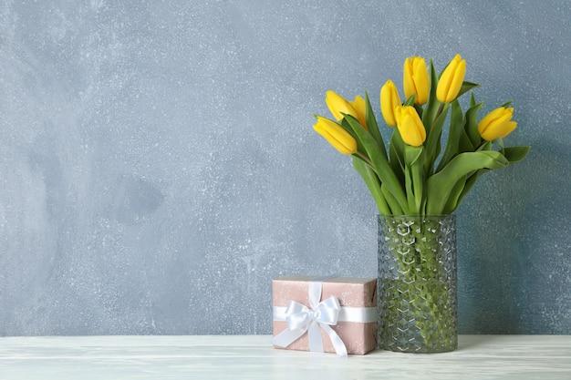Красивые желтые тюльпаны в стеклянной вазе на деревянный стол и место для текста