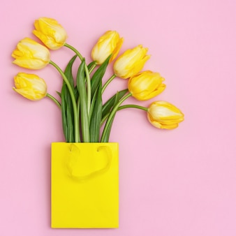 분홍색 배경에 종이 봉지에 아름 다운 노란 튤립. 봄 꽃 튤립과 자연 꽃 배경입니다.