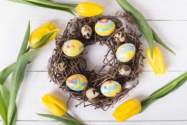 Beautiful yellow tulips with colorful quail and chicken eggs in wreath on white wooden table. spring and easter holiday concept.