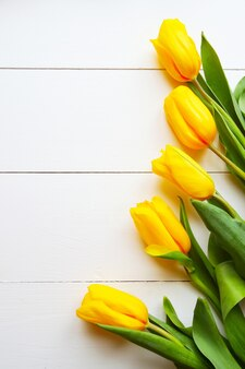 Beautiful yellow tulips on wooden white background, copyspace, top view