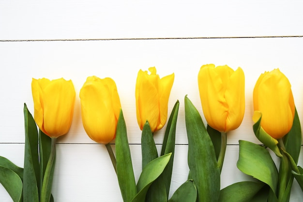 Beautiful yellow tulips on wooden white background, space for text. top view