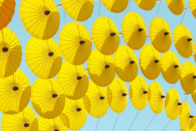 Beautiful yellow umbrellas background hanging in the sky
