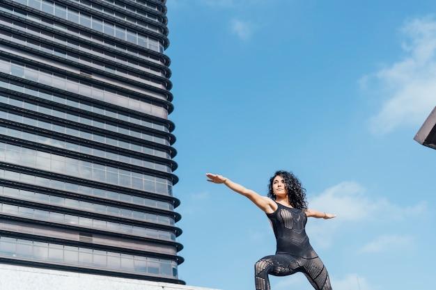 建物の間の大都会でヨガを練習する美しいヨギ女性。
