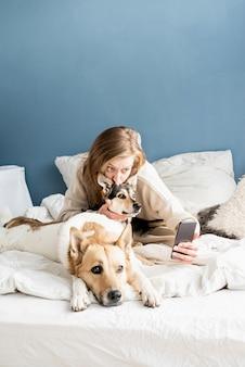 ベッドで朝に彼女の犬とスマートフォンでselfieを取っている美しい若い大人の陽気な女性