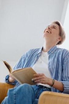 집에서 책을 읽고 커피를 마시는 아름다운 젊은 성인 유럽 여성