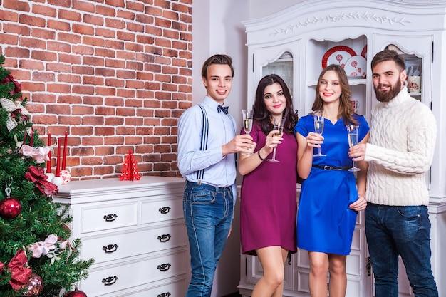 집에 있는 크리스마스 트리 근처에서 샴페인을 들고 토스트하는 아름다운 젊은 성인 친구들. 실내 촬영