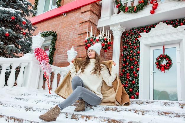 크리스마스 장식으로 집 현관에서 밝고 행복한 아름다운 젊은 성인 소녀