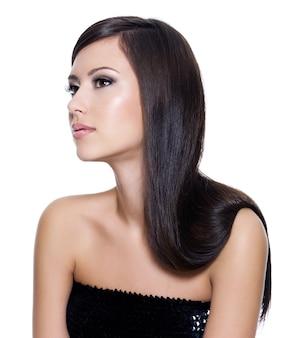 白い背景で隔離の長いストレートの美しさの髪のポーズの美しい若い大人の女の子