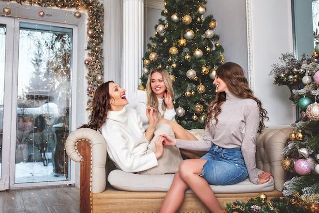 크리스마스 인테리어가 있는 방에서 밝고 행복한 아름다운 젊은 성인 여자친구