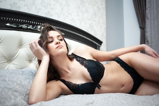 ランジェリーで横たわっている美しい若い大人のセクシーな女性。