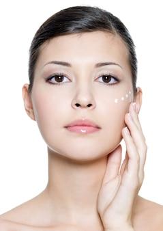Bella giovane donna adulta che applica crema cosmetica intorno all'occhio