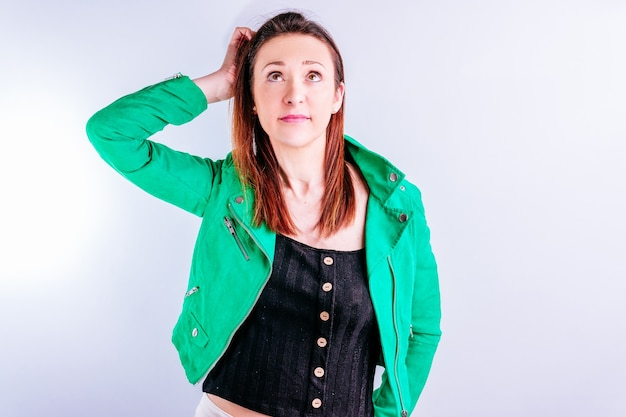 Beautiful young adult woman in green jacket scratching her head indecisively on white background with copyspace