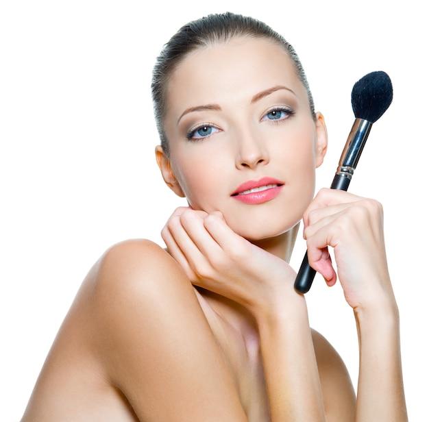 아름 다운 젊은 성인 여자는 흰색에 고립 된 루즈 또는 파우더를 적용하기위한 메이크업 brushe를 보유하고