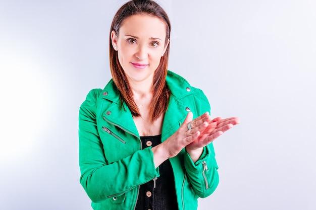 Красивая молодая взрослая женщина в зеленой куртке хлопая в ладоши, улыбаясь на белом фоне с copyspace.