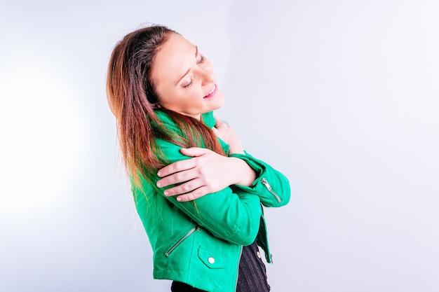 Красивая молодая взрослая женщина в зеленой куртке, обнимая себя с белым фоном с copyspace. концепция объятий