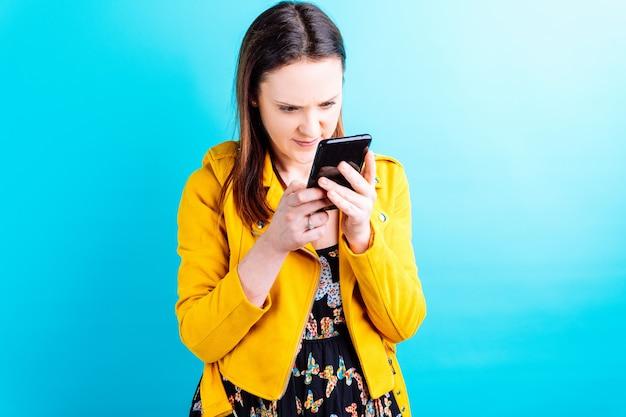 Красивая молодая взрослая женщина в желтой куртке на синем фоне, интенсивно глядя на смартфон. понятие зависимости от смартфона. сломанный смартфон