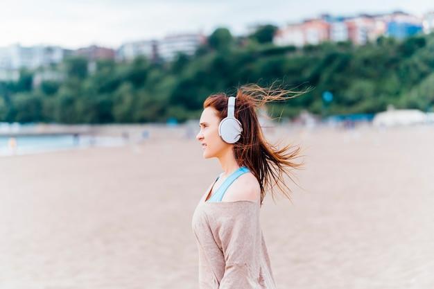 Красивая молодая взрослая женщина, слушающая музыку на пляже в пасмурный летний или весенний день в наушниках