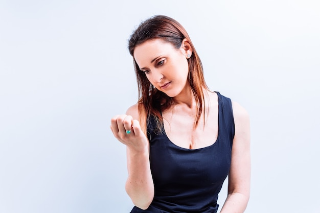 Beautiful young adult woman looking at her nails on white background