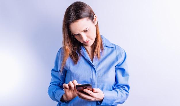 흰색 바탕에 모바일 스마트폰 기술 개념을 찾고 있는 아름다운 젊은 성인 여성
